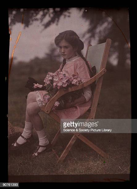 An autochrome of her daughter sitting in a garden chair holding a large bunch of freshly picked flowers taken by Etheldreda Janet Laing In the summer...