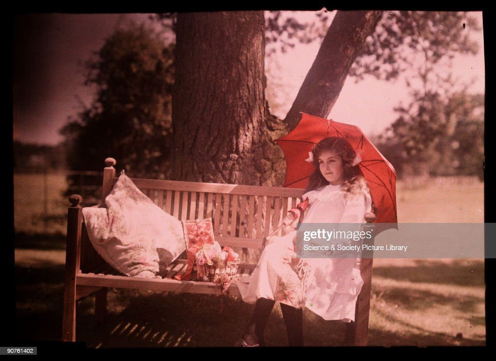 Girl with a parasol sitting on a bench, 1908. : Nieuwsfoto's