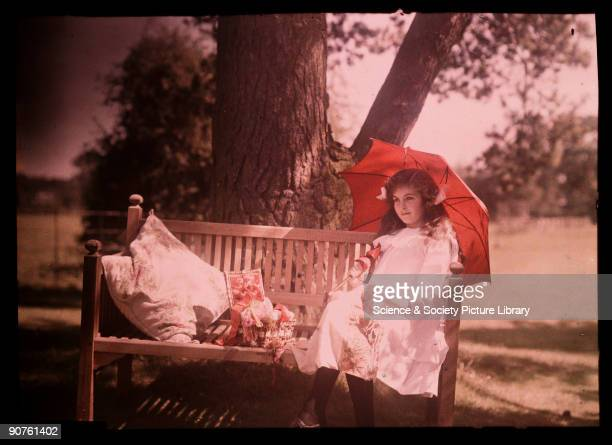 An autochrome of her daughter sitting under a tree taken by Etheldreda Janet Laing Next to her a basket overflows with ribbons and thread as she...