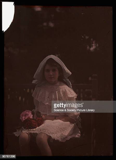 An autochrome of her daughter wearing a bonnet and lace dress holding a bunch of freshly picked red and pink roses taken by Etheldreda Janet Laing In...