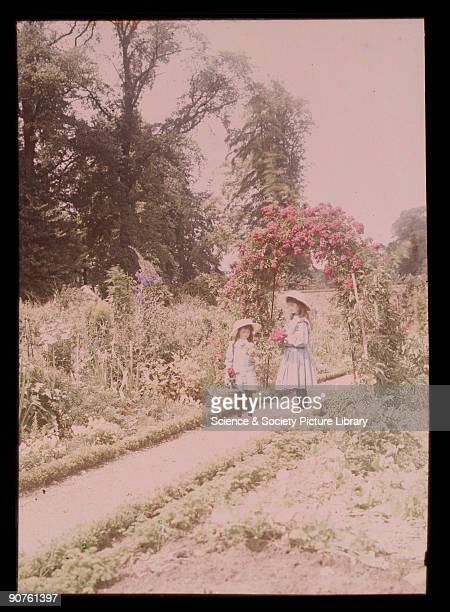 An autochrome of her daughters admiring their freshly picked flowers taken by Etheldreda Janet Laing The colourful flowers in the garden and on the...