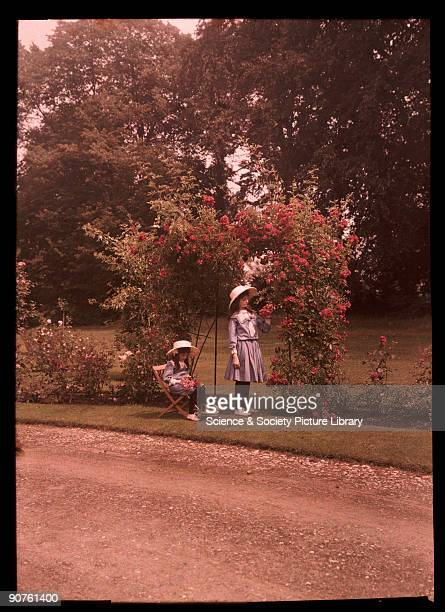 An autochrome of her daughters in a sunfilled garden taken by Etheldreda Janet Laing One girl picks red roses on the arched trellis The younger of...