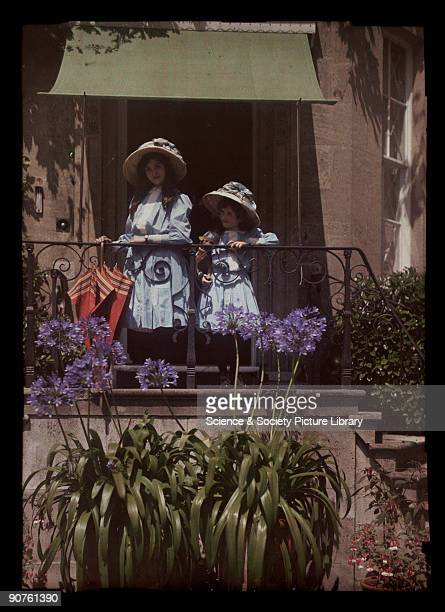 An autochrome of her daughters leaning on a balcony railing taken by Etheldreda Janet Laing The sunshine accentuates the bright colours of the girls'...