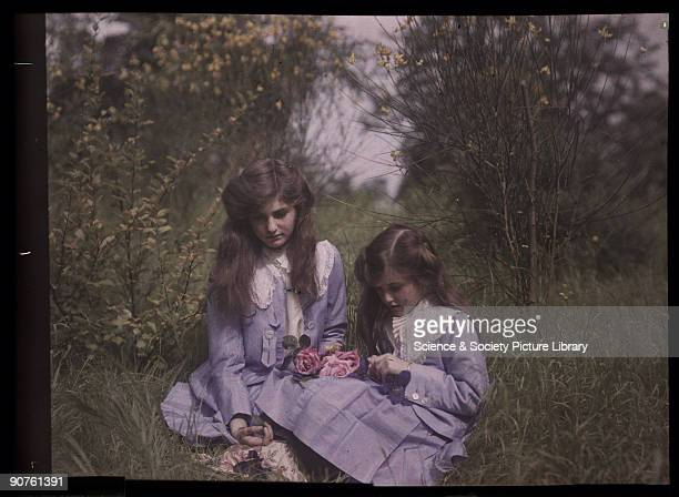 An autochrome of her daughters sitting in a garden tying roses together taken by Etheldreda Janet Laing In the summer of 1908 Laing took a series of...