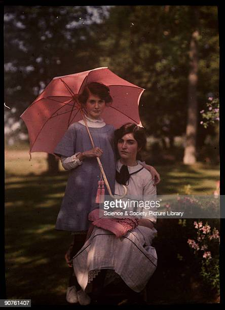 An autochrome of her daughters taken by Etheldreda Janet Laing The younger girl stands beside her sister holding a pink parasol The older girl rests...