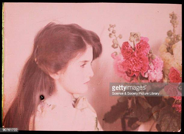 An autochrome portrait of a young girl looking at a vase of flowers taken by Etheldreda Janet Laing in about 1910 The young girl is probably one of...