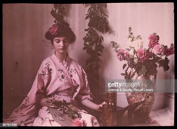 An autochrome portrait of her daughter dressed in a pink kimono taken by Etheldreda Janet Laing The design of the kimono is mirrored by the flower...