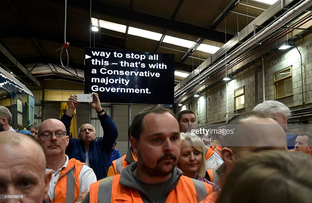 An autocue screen is seen behind Rail workers as Prime Minister David Cameron and Chancellor of the Exchequer George Osborne address guests during a visit to Arriva TrainCare mantenance plant in Crewe during the fourth week of their election campaign, on April 20, 2015 in Crewe, England. Britain goes to the polls in a General Election on May 7.