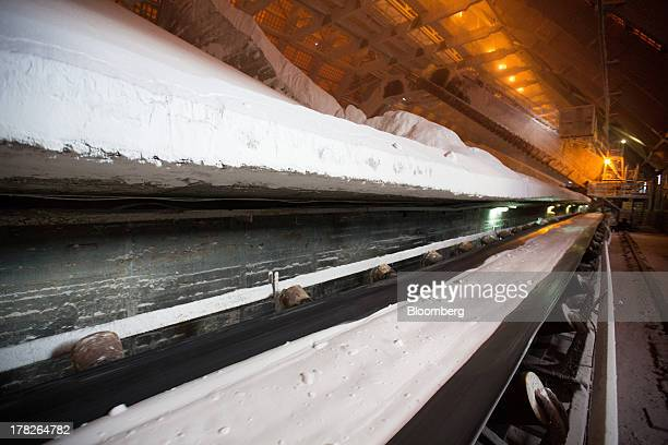 An automated conveyer belt system moves grains of potassium chloride also known as potash towards a storage area at the potash mine operated by OAO...