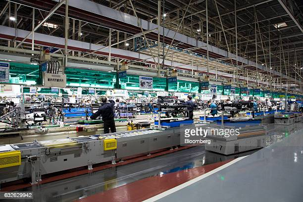 An automated guided vehicle right transports a vehicle module on a production line as employees work in the background at the Hyundai Mobis Co...