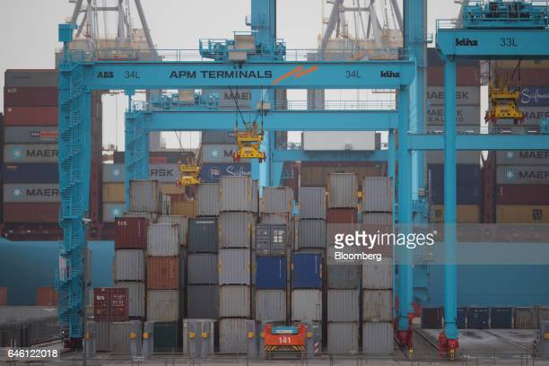 An automated guided vehicle sits beside stacks of shipping containers as cranes operate at the APM container terminal in the Port of Rotterdam in...