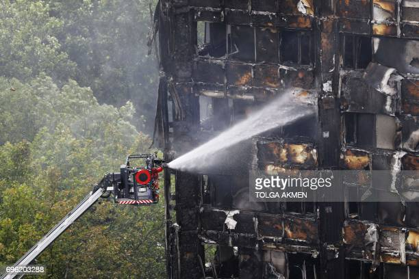 TOPSHOT An automated hose sprays water onto Grenfell Tower a residential tower block in west London that was caught in a huge blaze on June 15 2017...