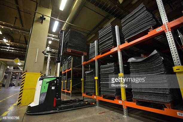 An automated laserguided loading vehicle stacks lengths of rubber into storage areas ahead of moulding inside the Vsevolozhsk tyre manufacturing...