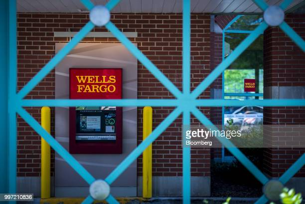 An automatic teller machine is seen behind a fence at a Wells Fargo Co bank branch in Schaumburg Illinois US on Tuesday July 10 2018 Wells Fargo Co...