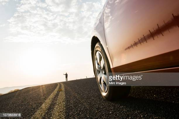 an automobile approaching a person standing on the side of a road. - タイヤ ストックフォトと画像
