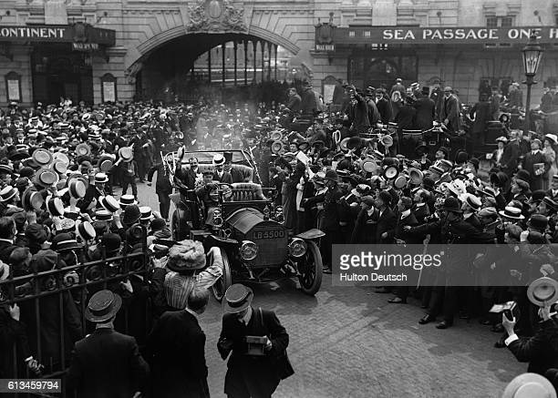 An automobile carrying English publisher Lord Northcliffe and French pilot Louis Bleriot makes its way past cheering crowds Bleriot became the first...