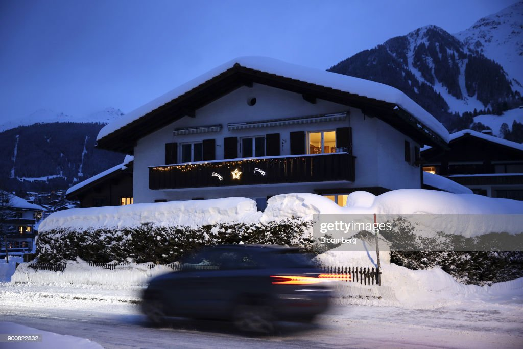 An automobile drives past a residential property illuminated at dusk in Klosters, Switzerland, on Saturday, Dec. 30, 2017. The supply of uninhabited apartments for rent has increased faster than the Swiss population has grown. Photographer: Stefan Wermuth/Bloomberg via Getty Images