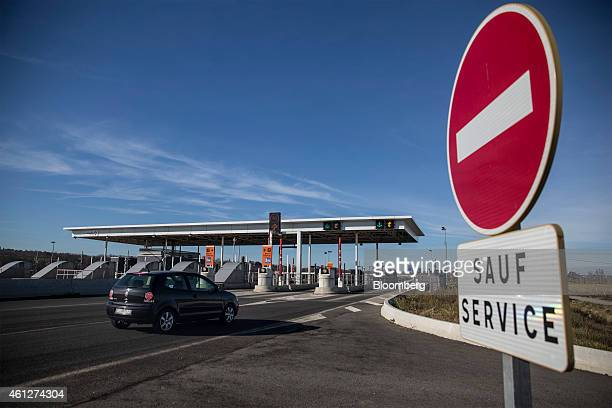 An automobile drives towards a tollbooth as they enter the A61 motorway operated by Autoroutes du Sud de la France a division of Vinci SA near...