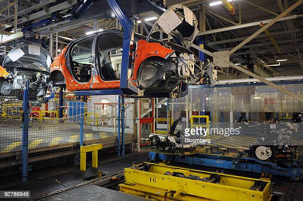 An automobile is seen raised on the assembly line at the PSA Peugeot Citroen factory in Poissy near Paris France on Wednesday Nov 4 2009 French car...