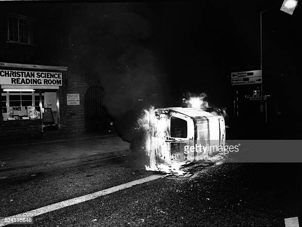 An automobile on fire during the 1984 Brixton riots London England