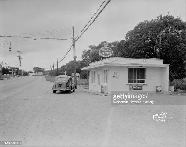 An automobile parked in front of the West Side Fountain operated by John P Stein and Joseph Scalissi with Borden's Ice Cream Dr Pepper Pepsi and...