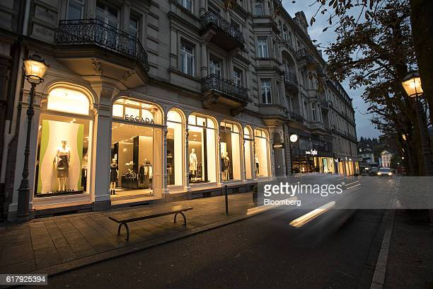An automobile passes an Escada luxury clothing store at dusk in BadenBaden Germany on Monday Oct 24 2016 The world's luxurygoods market stopped...