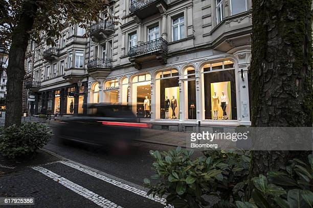 An automobile passes an Escada luxury clothing store in BadenBaden Germany on Monday Oct 24 2016 The world's luxurygoods market stopped growing this...