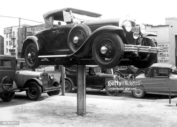An automobile perched on an Elder Auto Lift at an outdoor repair shop Los Angeles California 1928