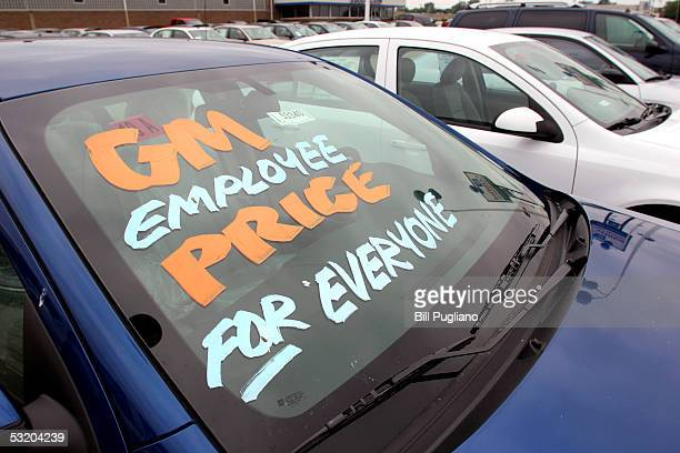 An automobile windshield ad at a General Motors Chevrolet dealership announces GM's new incentive program which allows all buyers to be eligible for...