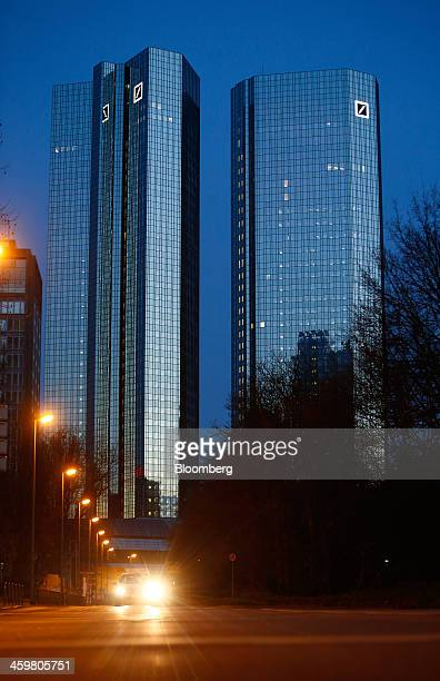 An automobile's headlights illuminate a road as the Deutsche Bank AG headquarters stands beyond in Frankfurt Germany on Tuesday Dec 31 2013 Deutsche...