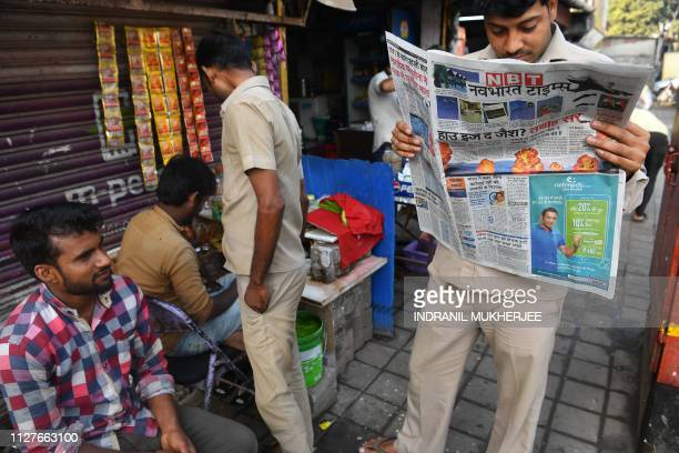 An autorickshaw driver reads a newspaper with front page reports on the Indian air strikes against militant camps in Pakistan's territory in Mumbai...