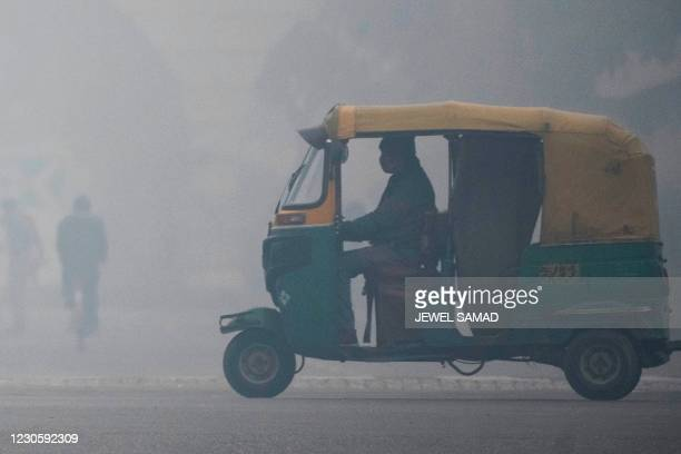 An auto-rickshaw driver rides along a street amid heavy smog conditions in New Delhi on January 15, 2021.