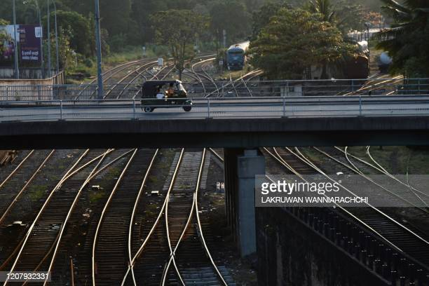 An autorickshaw driver rides through an empty bridge after the authorities announced a weekend curfew in the country as a preventive measure against...