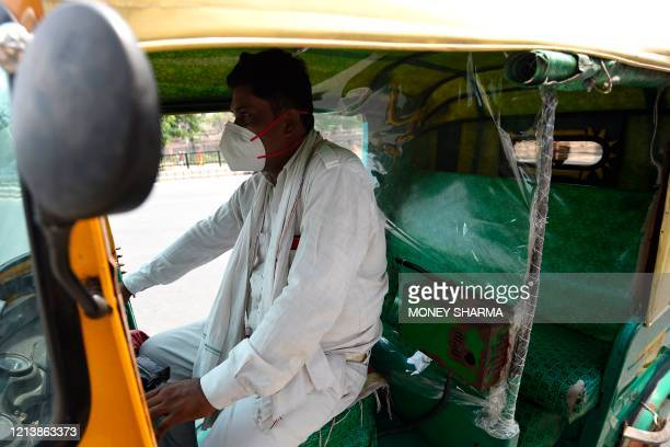 An auto-rickshaw driver wearing a facemask waits for passengers after the government eased restrictions imposed as a preventive measure against the...