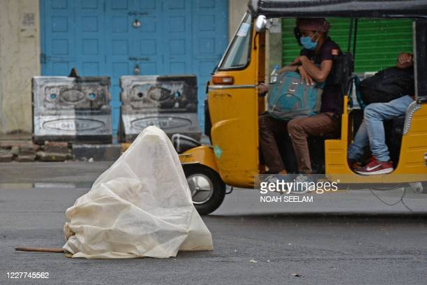 An auto-rickshaw passes by a homeless man sitting on a road under a metro rail bridge as he covers himself with a polythene sheet during a monsoon...