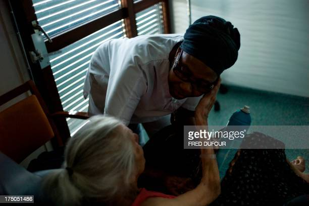 An auxiliary nurse speaks with a patient at the geriatric area of the Argenteuil hospital in a Paris suburb on July 22 2013 AFP PHOTO / FRED DUFOUR /...