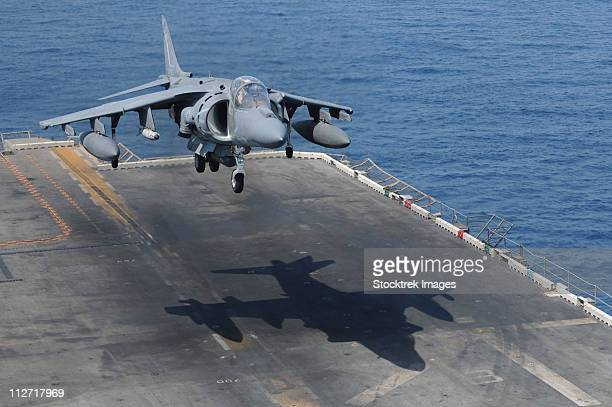 an av-8b harrier aircraft lands on the flight deck of uss peleliu. - aircraft carrier stock pictures, royalty-free photos & images