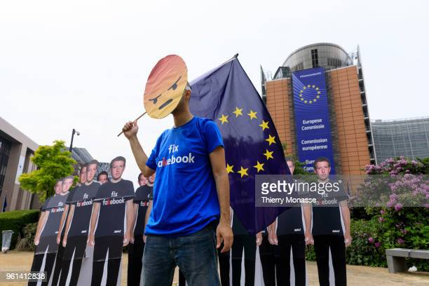 An Avaaz activist attends an antiFacebook demonstration with cardboard cutouts of Facebook chief Mark Zuckerberg on which is written Fix Fakebook in...