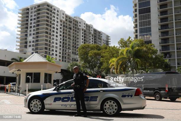 An Aventura City police officer stands across the street from the condo building that has a possible connection to alleged bomber Cesar Sayoc and his...