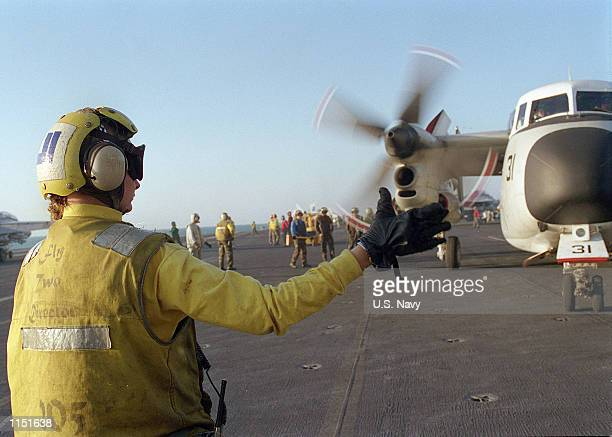 """An Aviation Boatswain's Mate directs a C-2 """"Greyhound"""" for mail delivery on board the aircraft carrier USS Carl Vinson January 4,1999. Vinson..."""