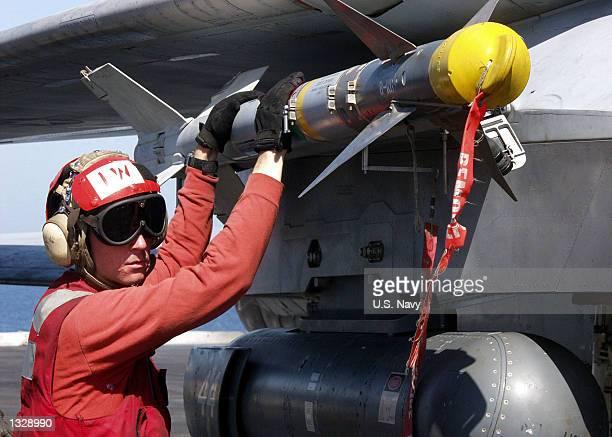 "An Aviation Ordnanceman checks an AIM-9 ""Sidewinder"" missile on an F-14 Tomcat October 21, 2001 aboard the aircraft carrier USS Carl Vinson. The Carl..."