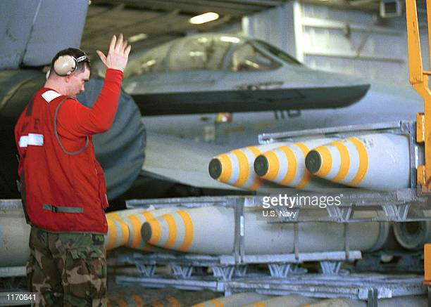 An Aviation Ordnanceman directs a forklift while moving bombs in the hanger bay October 18, 2001 aboard the aircraft carrier USS Carl Vinson. The...