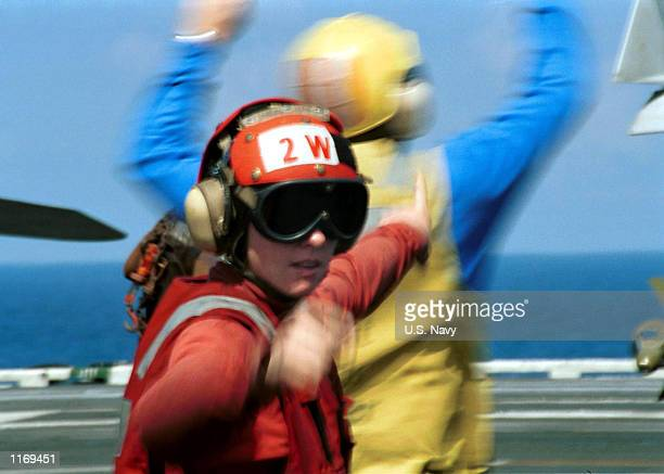 An Aviation Ordnanceman gives the signal to have her crew prepare aircraft for arming October 13, 2001 aboard the aircraft carrier USS Carl Vinson...