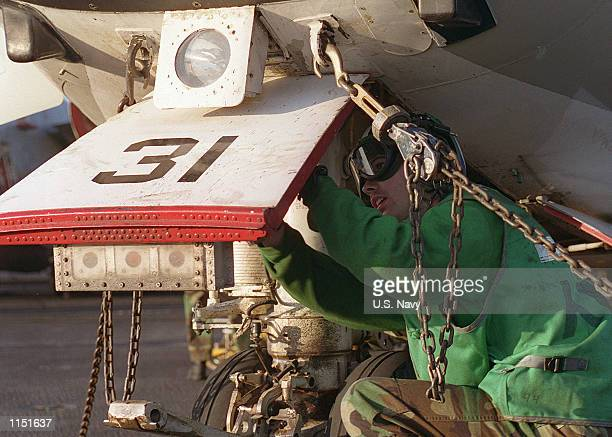 """An Aviation Structural Mechanic performs a turn around inspection on a C-2 """"Greyhound"""" on board the aircraft carrier USS Carl Vinson January 4, 1999...."""