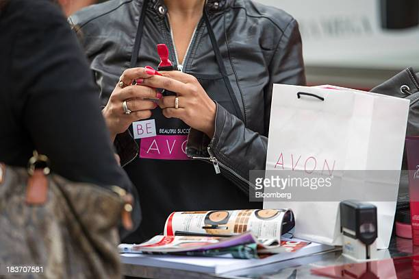 An Avon Products Inc sales representative holds beauty products during an Avon Magic Bus recruiting event in the Bronx borough of New York US on...