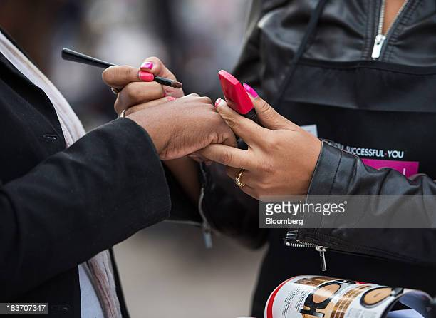 An Avon Products Inc sales representative samples beauty products during an Avon Magic Bus recruiting event in the Bronx borough of New York US on...