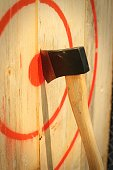 An axe stuck in a wooden target