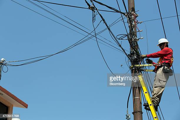 An Axtel SAB technician installs fiber optic cable at a home in Mexico City Mexico on Thursday April 23 2015 In March Axtel settled a decadelong...
