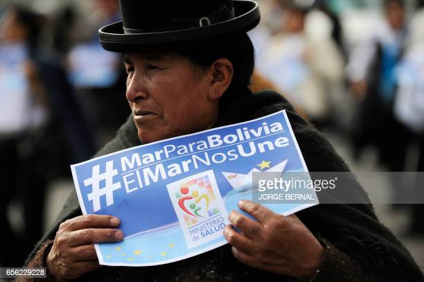 An Aymara indigenous woman holds a sign reading 'Sea for Bolivia The sea unites us' during the 'Marea Azul' march called by the Bolivian Navy on...
