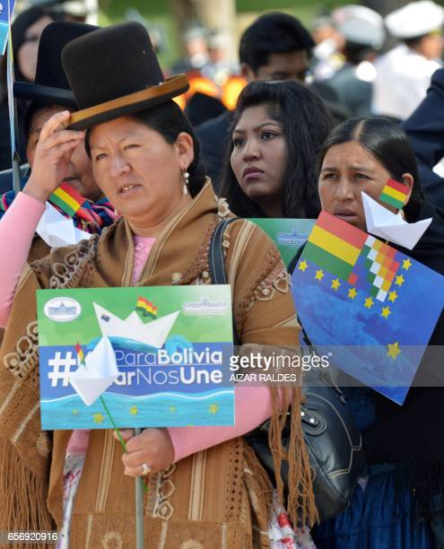 An Aymara indigenous woman holds a sign reading 'Sea for Bolivia' during the ceremony that marks the 138th anniversary of the Calama battle against...